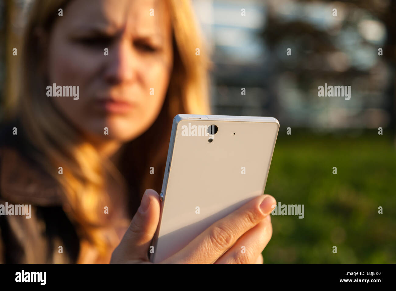 annoyd woman with smartphone in sunlight - Stock Image