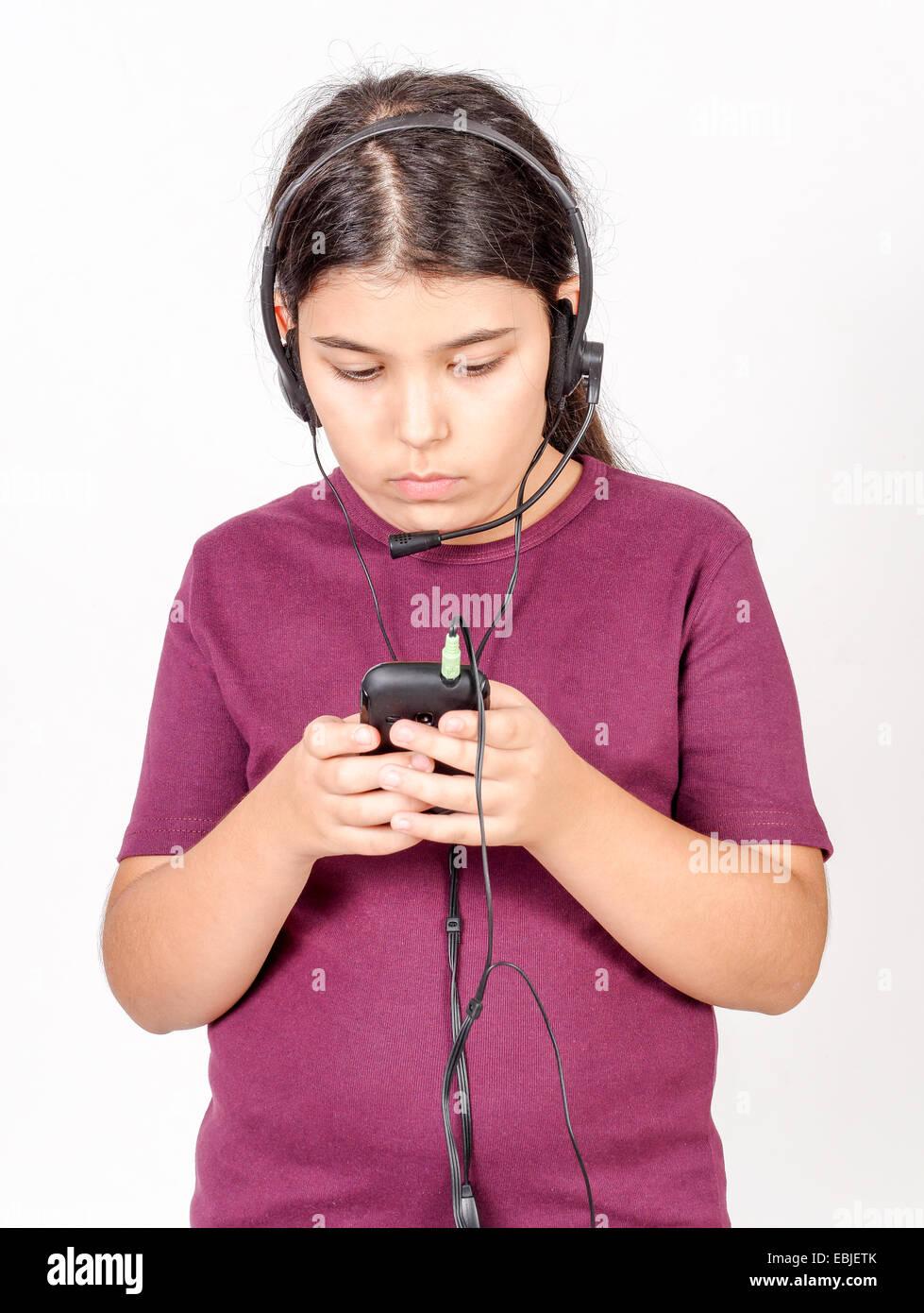 Girl of 9 listens to music on headphones - Stock Image