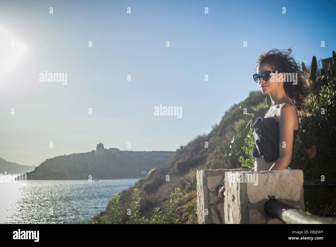 Young woman looking at view of the sea - Stock Image