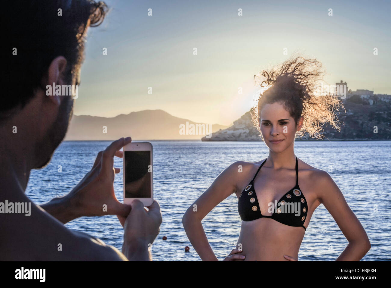 Man photographing young woman on vacation - Stock Image