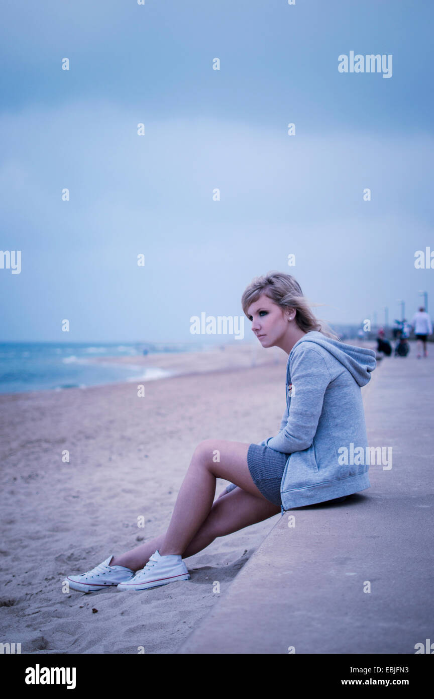 Young woman sitting on sea wall, looking out to sea - Stock Image