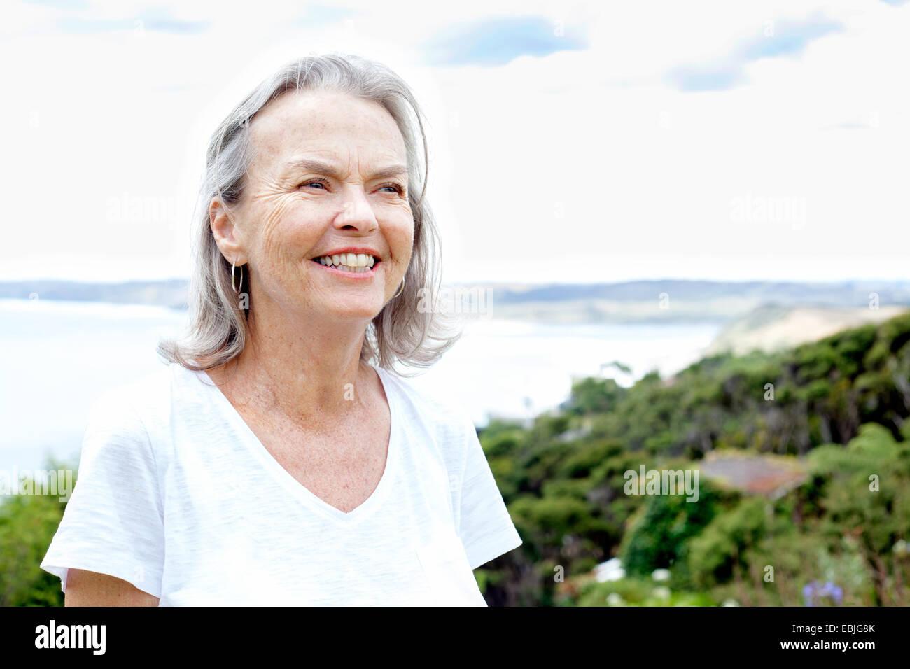 Senior woman, ocean in background, Raglan, New Zealand - Stock Image