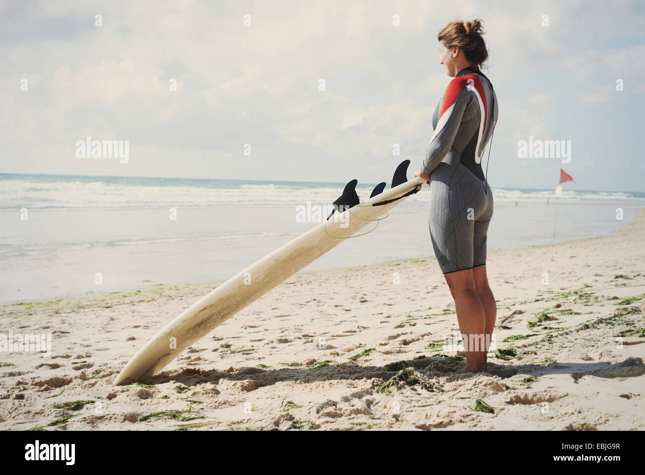 Surfer with surfboard on beach, Lacanau, France - Stock Image