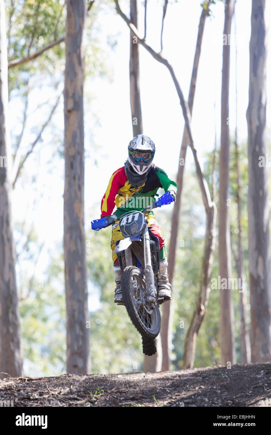 Young male motocross rider jumping mid air in forest - Stock Image