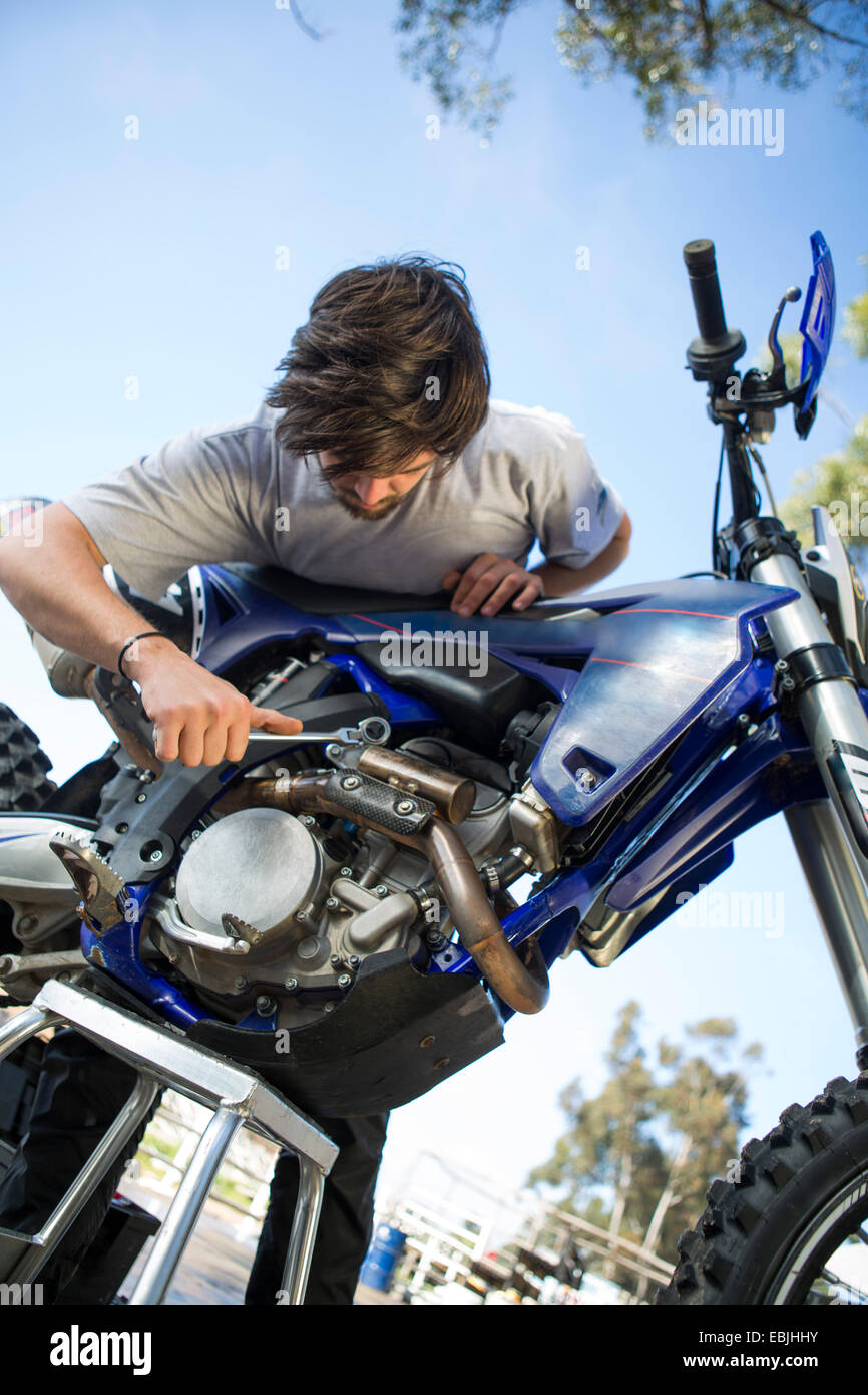 Young male motocross racer adjusting motorcycle engine in forest - Stock Image