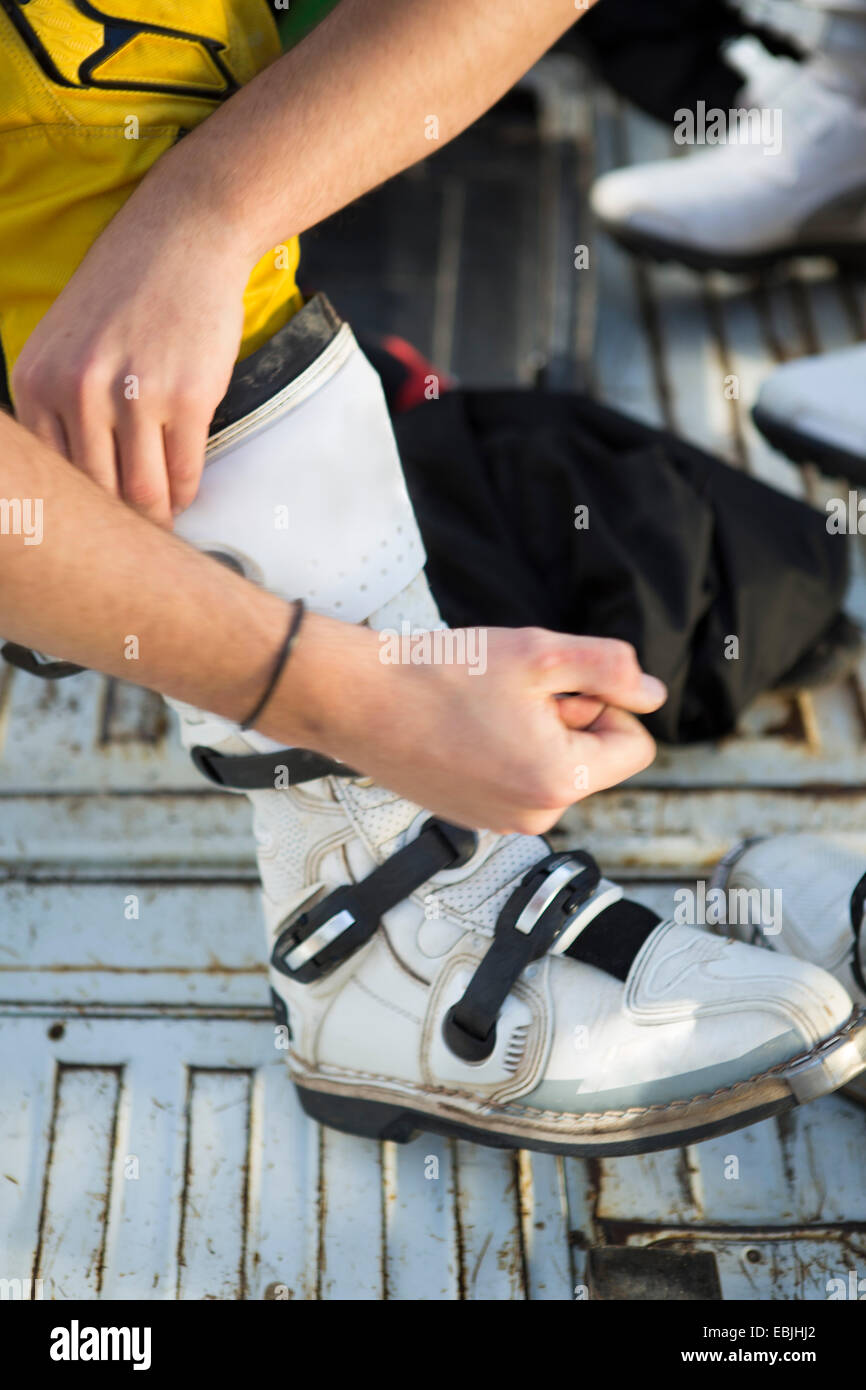 Close up of motocross motorcycle competitor fastening boot - Stock Image
