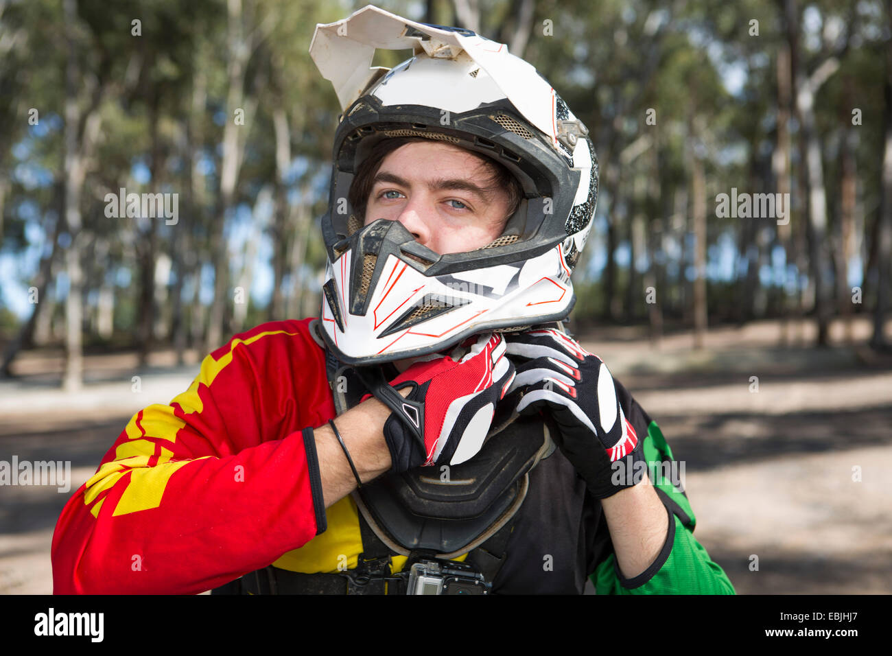 Motocross motorcycle competitor fastening helmet in forest - Stock Image