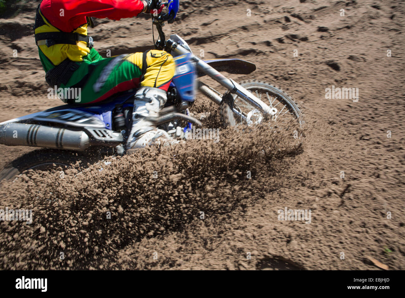 Young male motocross rider racing through mud track - Stock Image