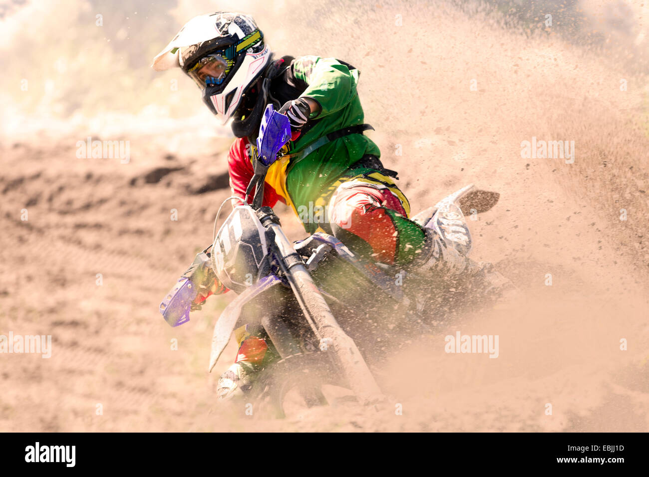 Young male motocross rider racing and leaning into mud track - Stock Image