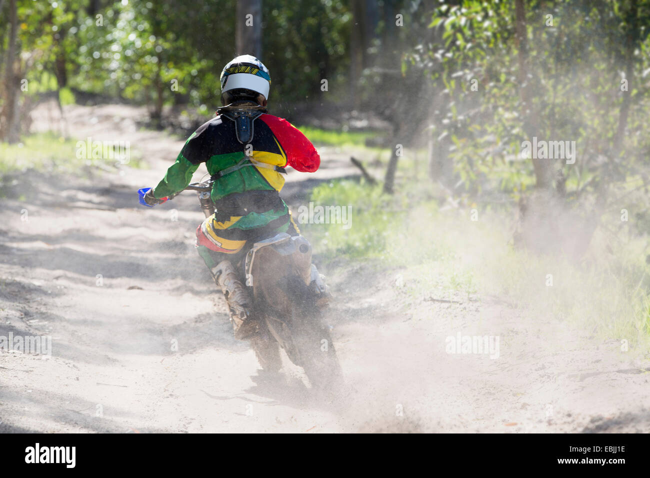 Rear view of young male motocross rider racing on forest track - Stock Image