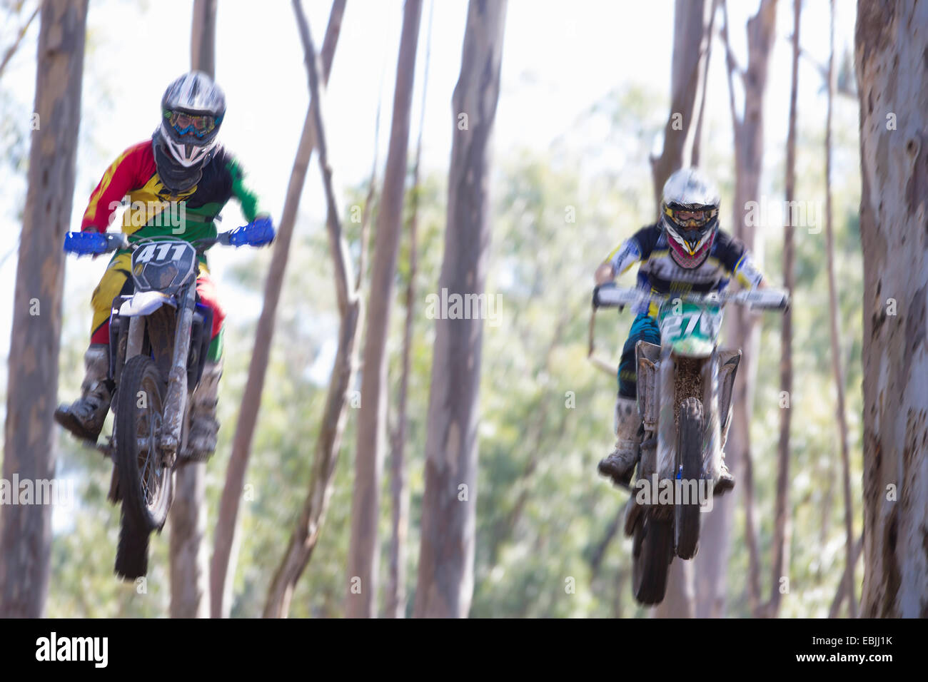 Two young male motocross riders jumping mid air through forest - Stock Image