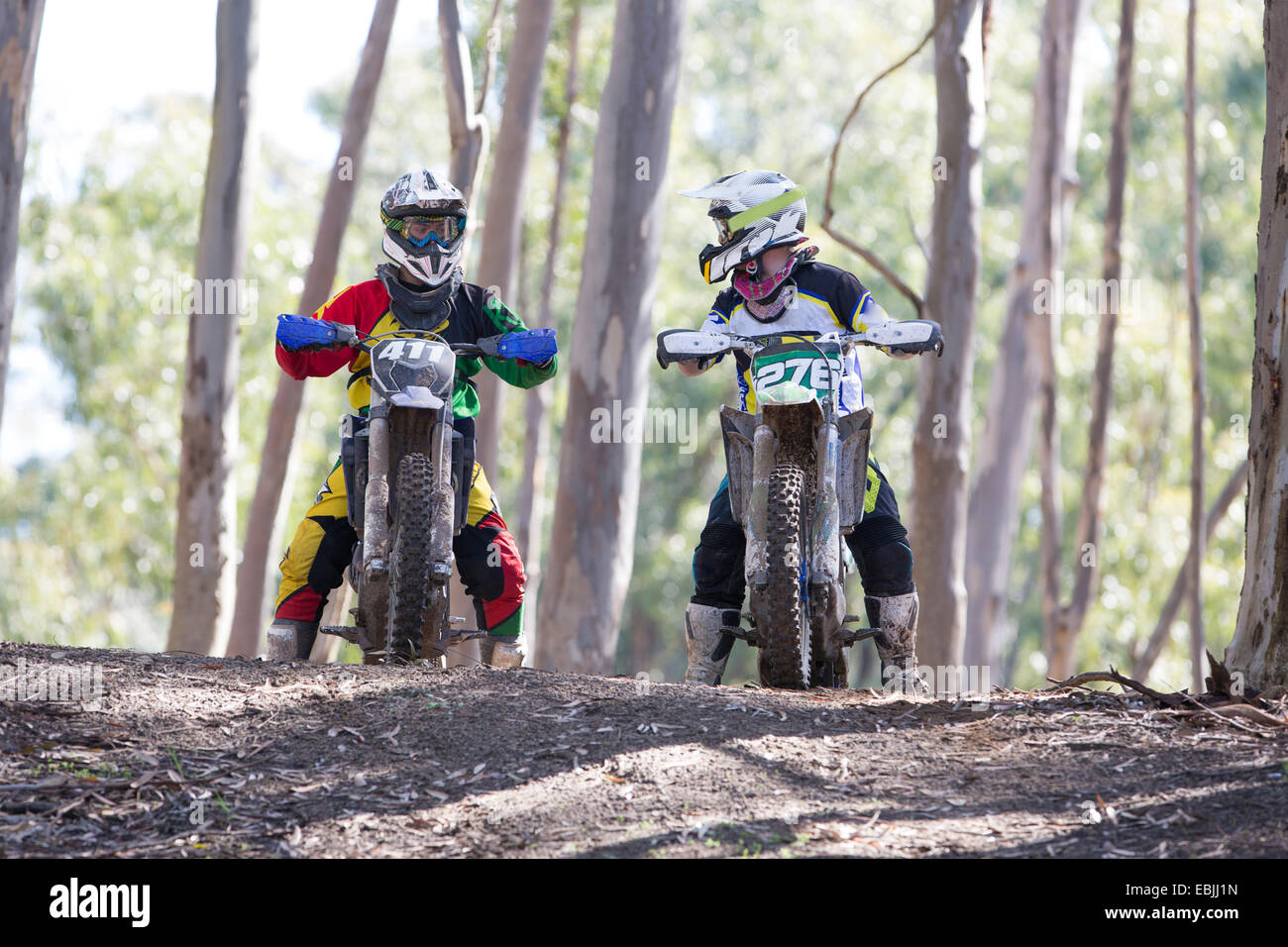 Two young male motocross riders chatting in forest - Stock Image
