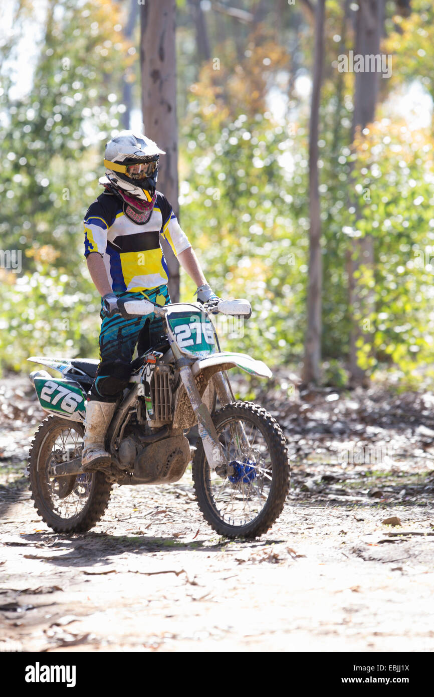 Young male motocross racer standing whilst riding through forest - Stock Image