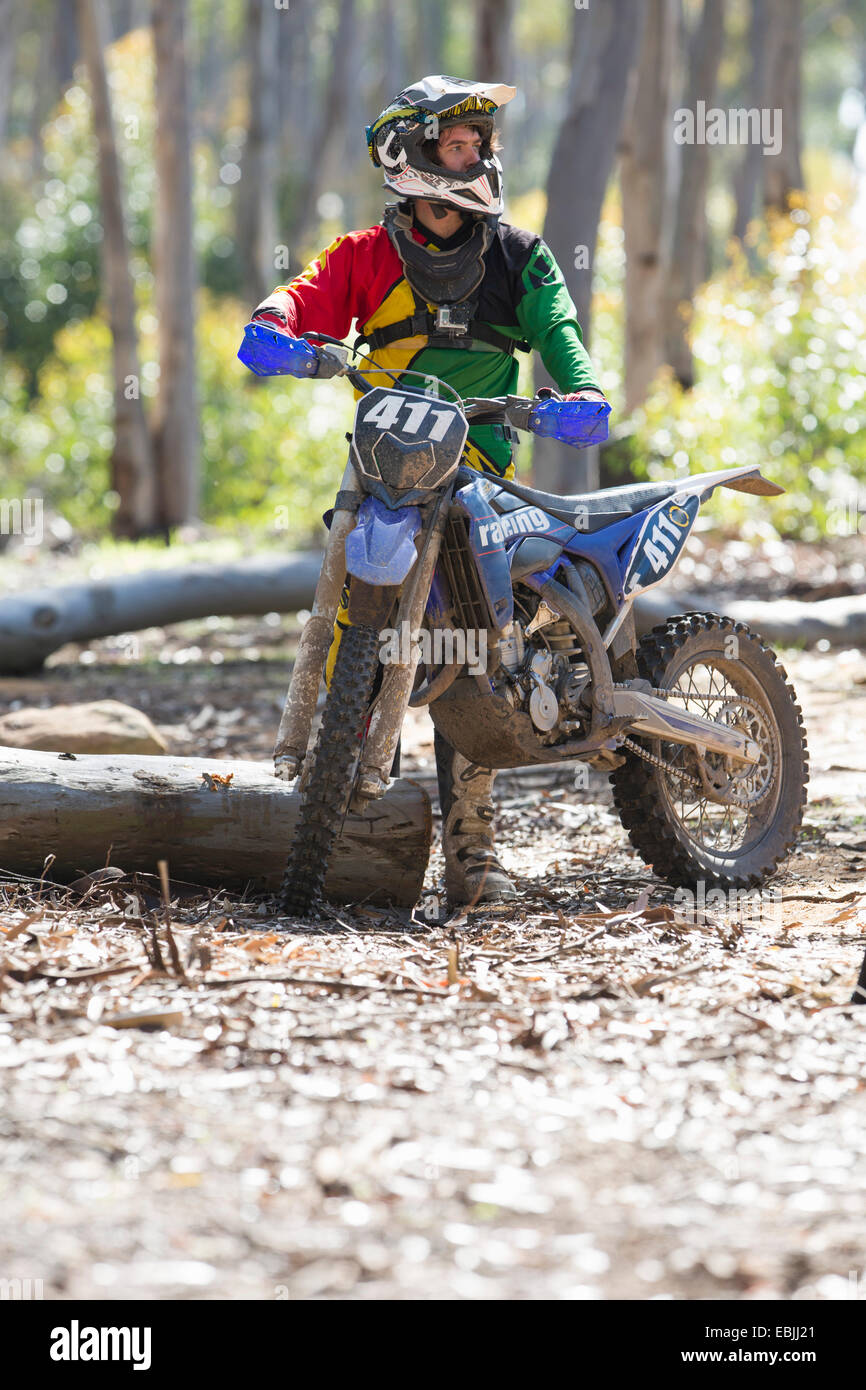 Young male motocross racer standing in forest - Stock Image