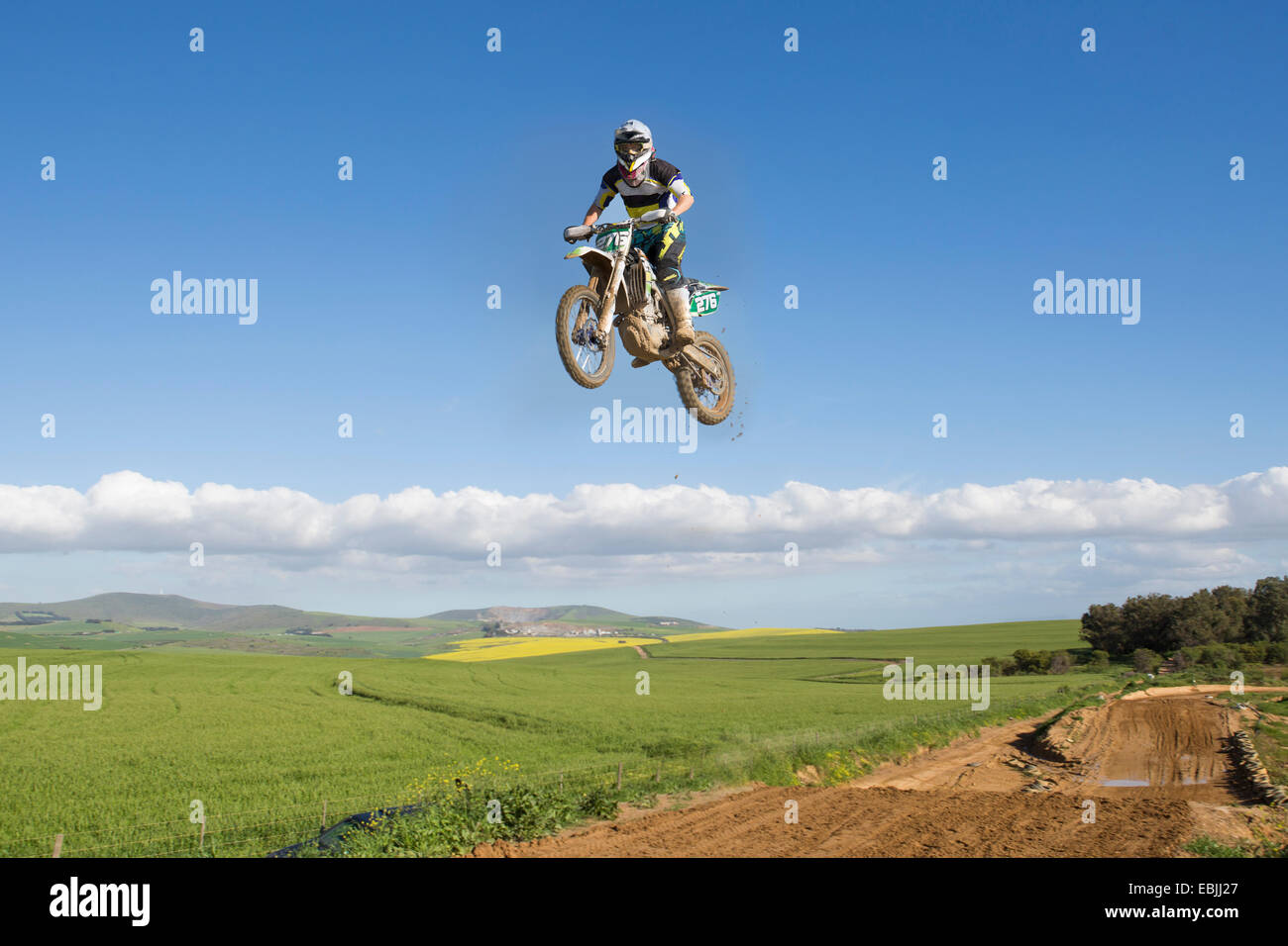 Young male motocross racer jumping mid air over landscape - Stock Image