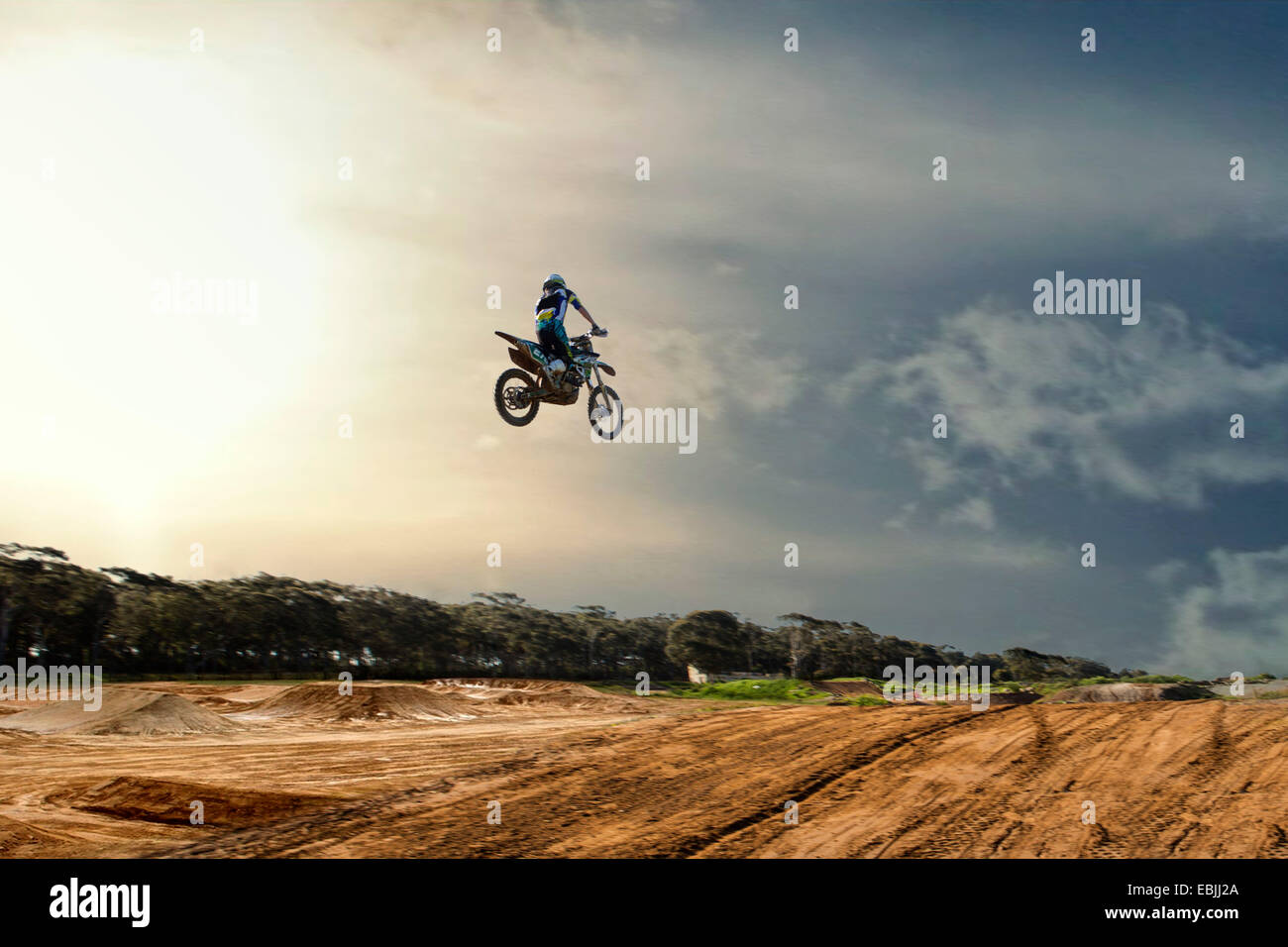 Silhouetted young male motocross racer jumping mid air over mud track - Stock Image