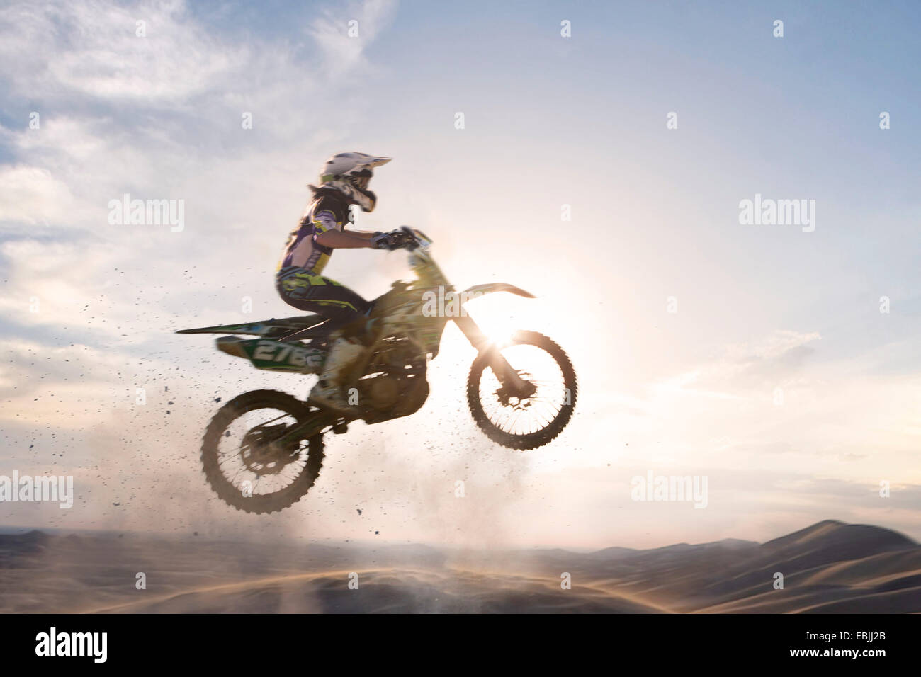 Silhouetted young male motocross racer jumping over mud track - Stock Image