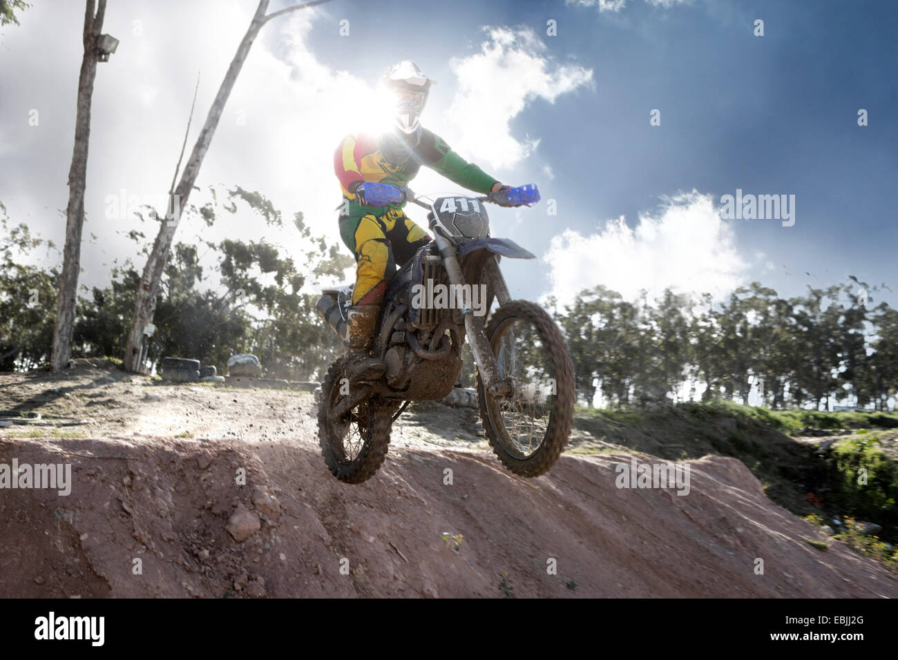 Young male motocross racer jumping mid air down mud hill - Stock Image