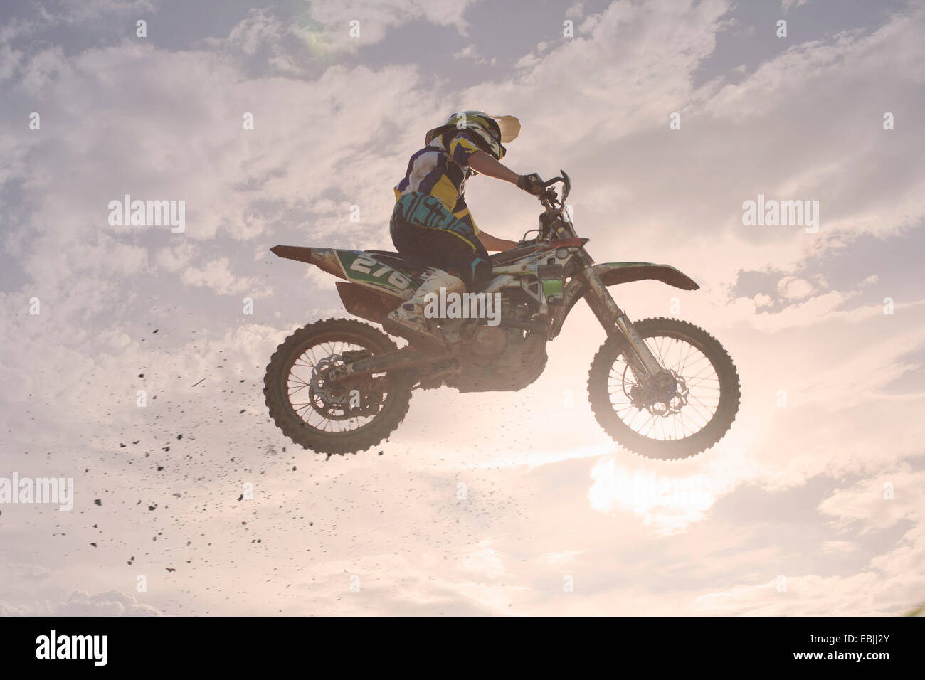 Silhouetted young male motocross racer jumping mid air - Stock Image