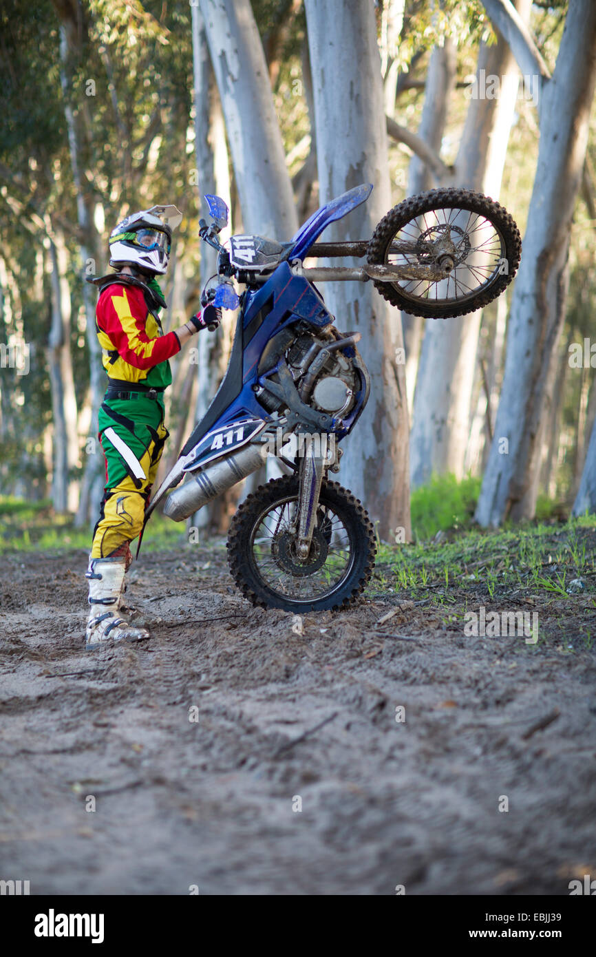 Young male motocross racer standing with motorcycle on forest track - Stock Image