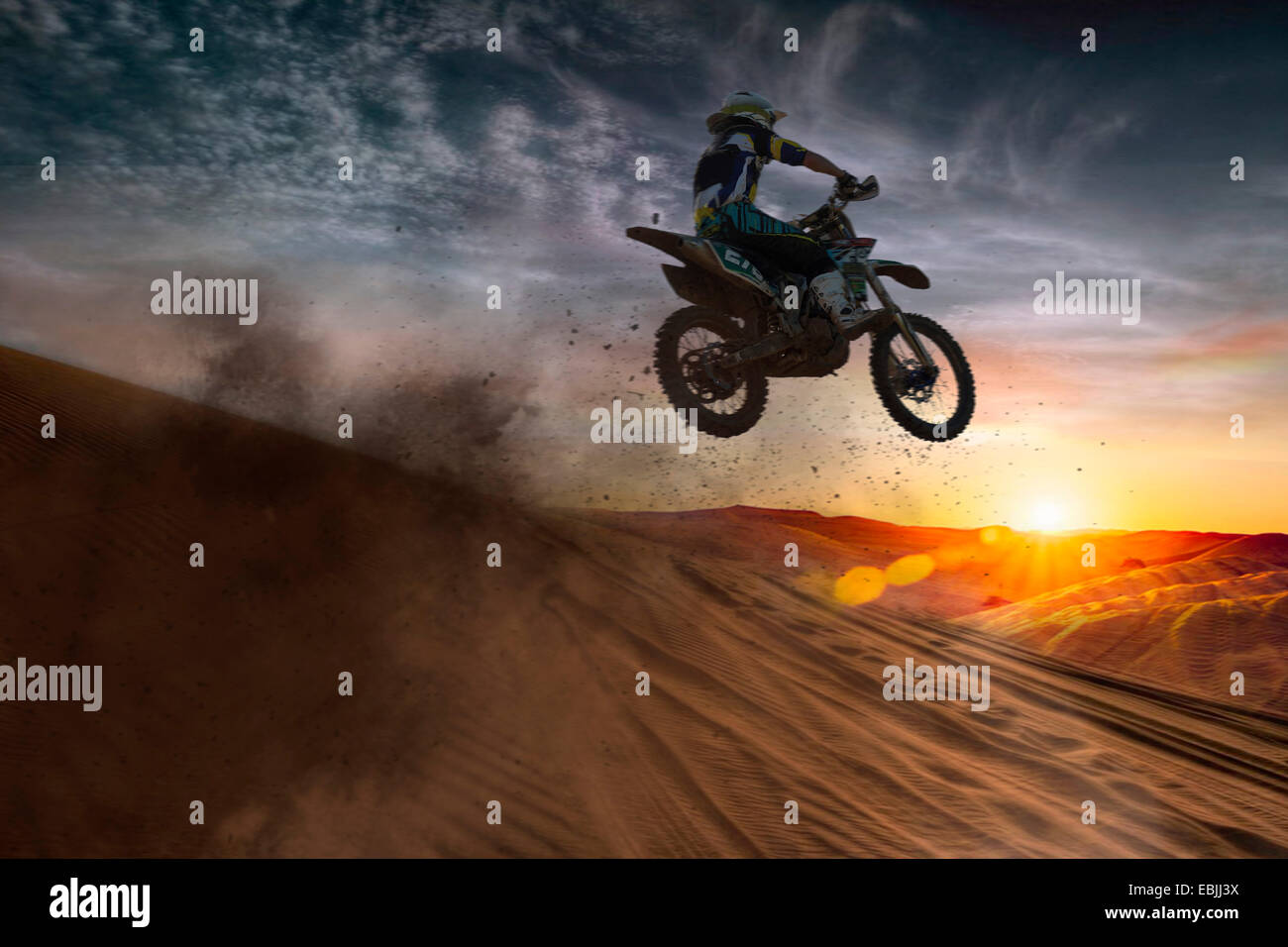 Young male motocross racer jumping mid air at sunset - Stock Image