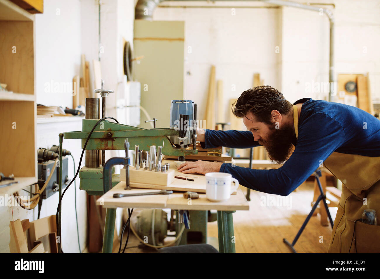 Mid adult craftsman using machine in pipe organ workshop - Stock Image