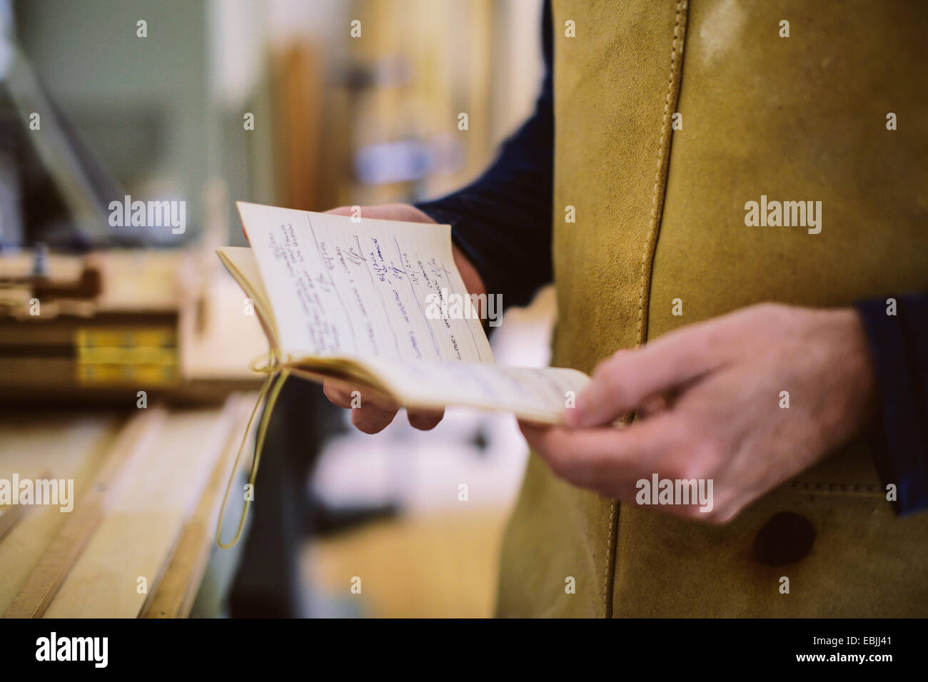 Close up of mid adult craftsman holding notebook in organ workshop - Stock Image