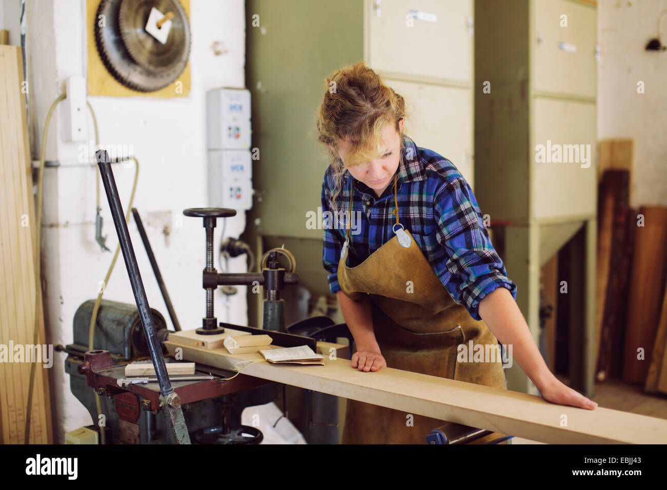 Young craftswoman checking wood in pipe organ workshop - Stock Image