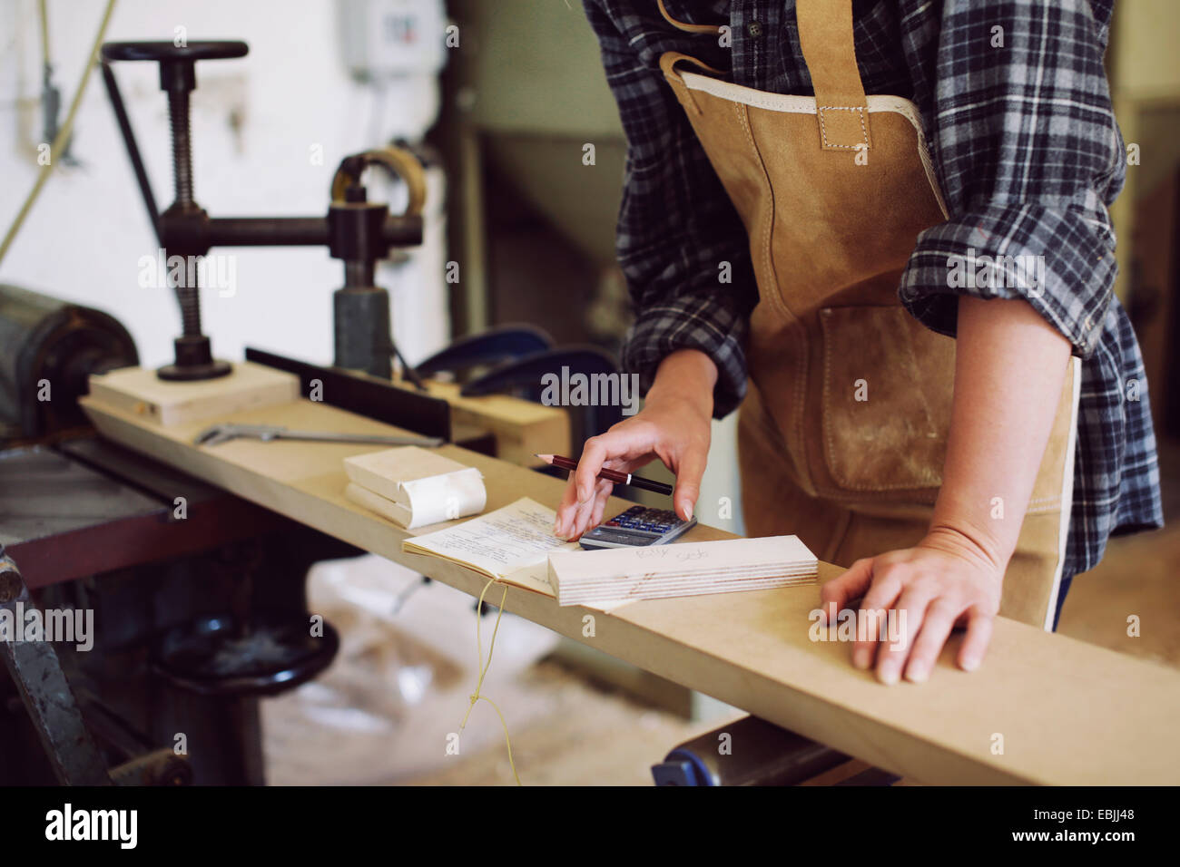 Cropped shot of young craftswoman using calculator in pipe organ workshop - Stock Image