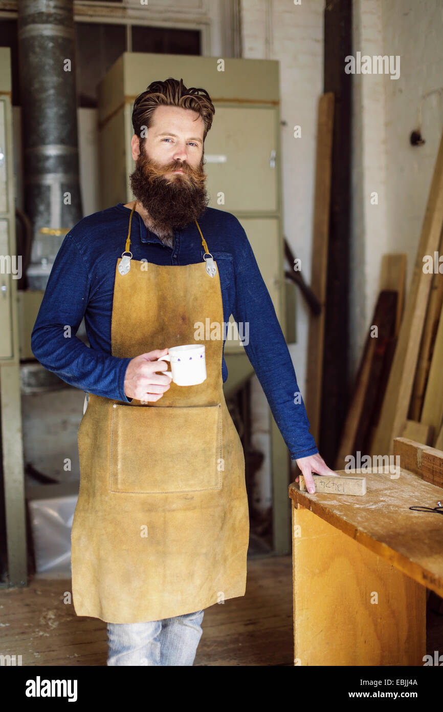 Portrait of mid adult craftsman drinking coffee in organ workshop - Stock Image