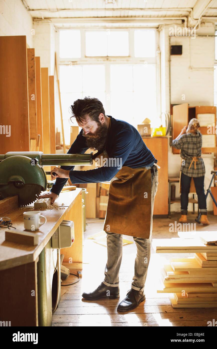 Mid adult craftsman using machinery in organ workshop - Stock Image