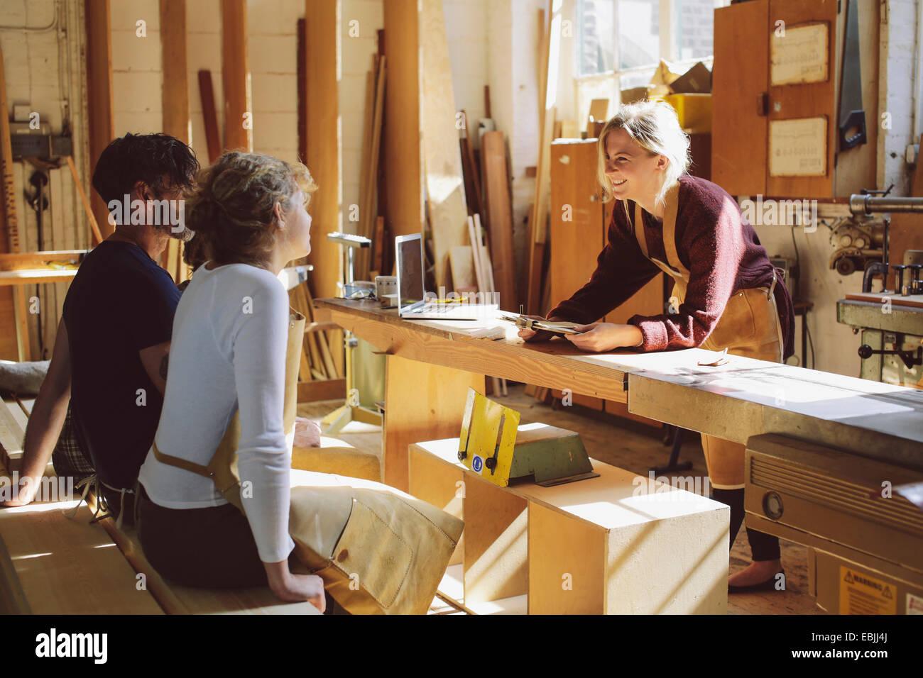 Three craft workers having an informal meeting in pipe organ workshop - Stock Image