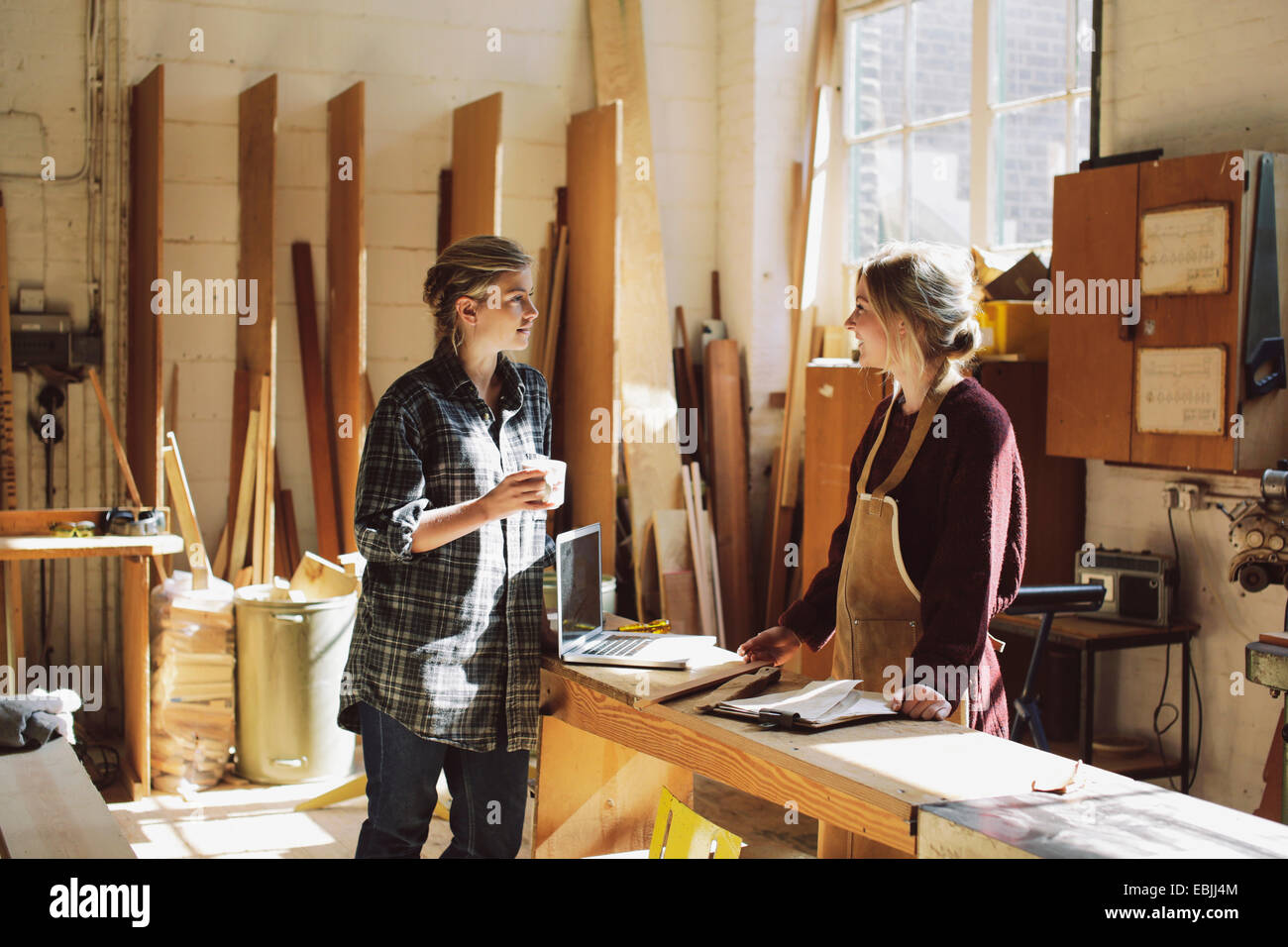 Two craftswomen drinking coffee in pipe organ workshop - Stock Image