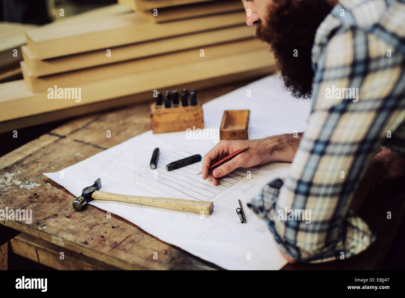 Cropped shot of mid adult craftsman looking down at blueprint in organ workshop - Stock Image