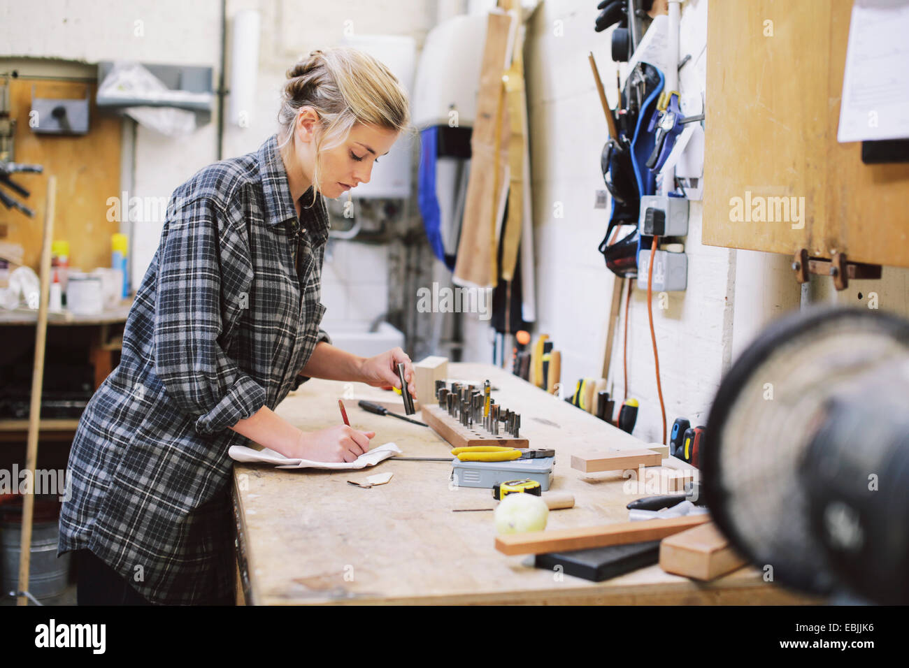 Young craftswoman making notes at workbench in pipe organ workshop - Stock Image