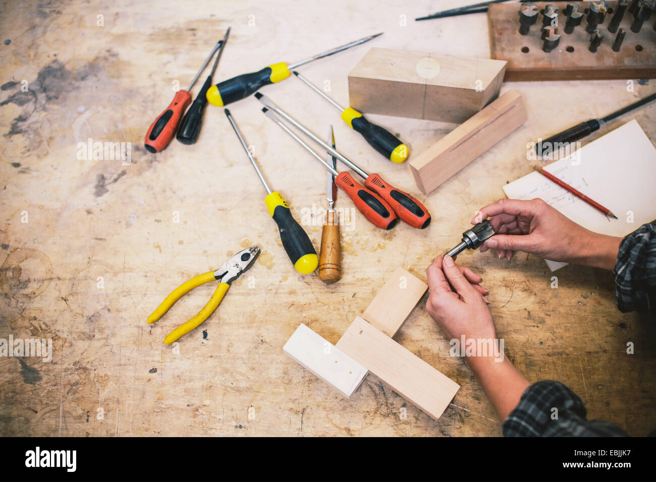 Hands of young craftswoman holding component in pipe organ workshop - Stock Image