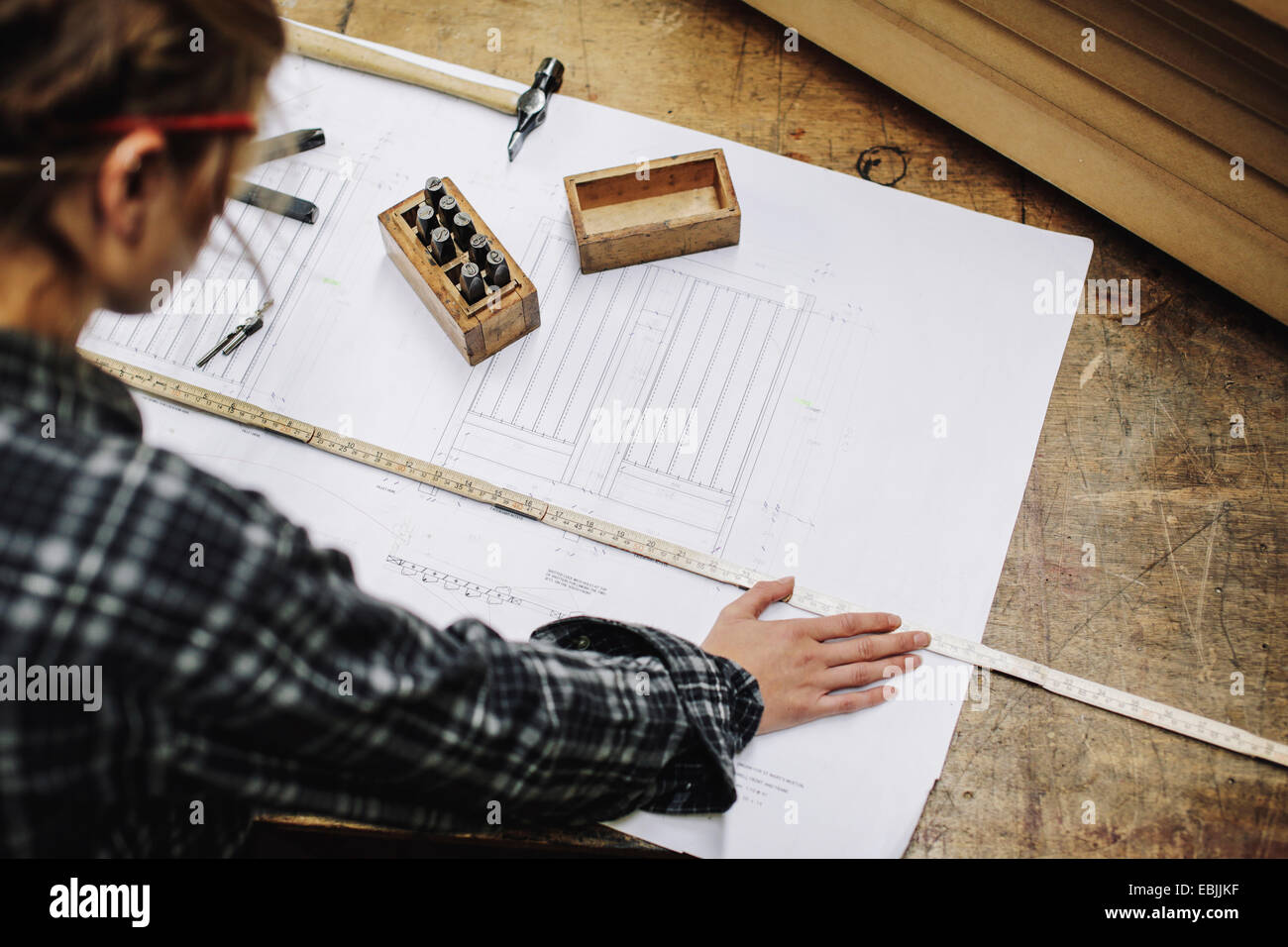 Young craftswoman measuring blueprint in pipe organ workshop - Stock Image