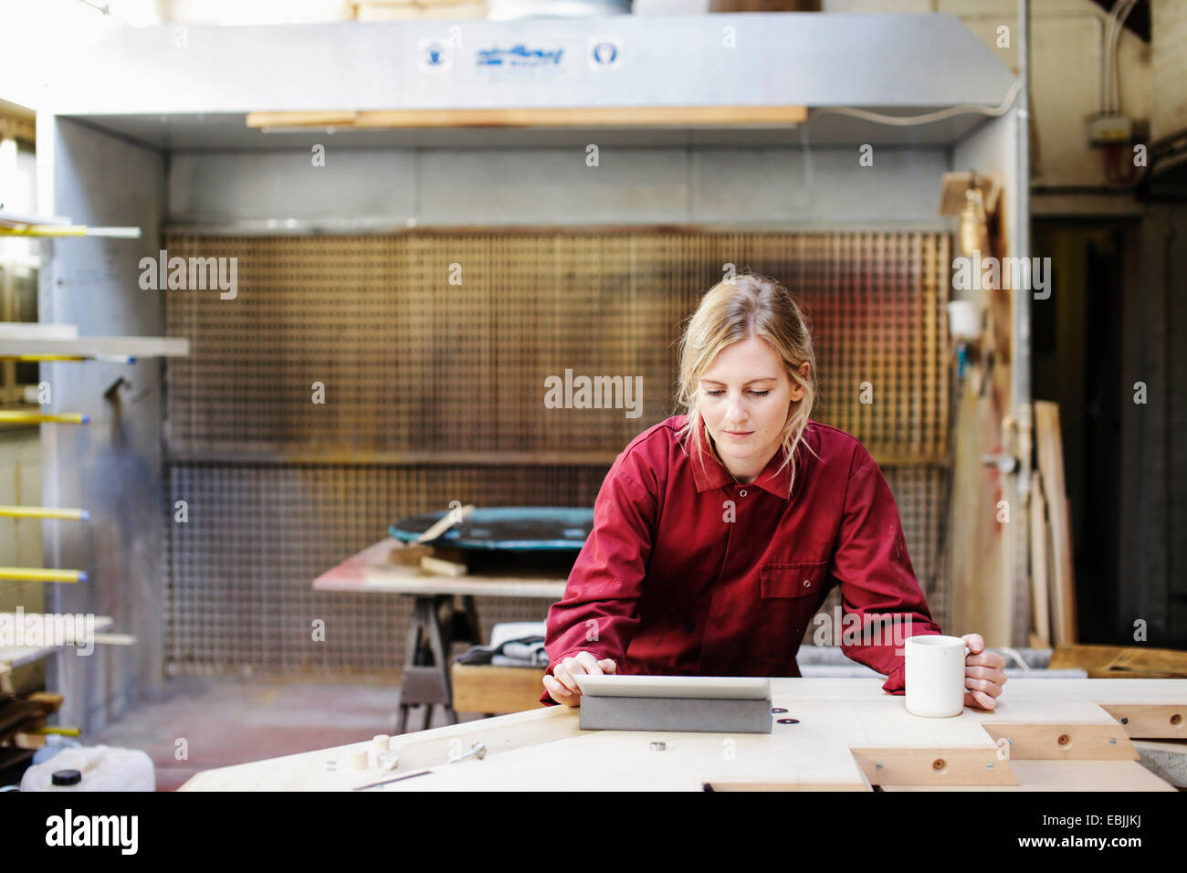 Young craftswoman using digital tablet in pipe organ workshop - Stock Image