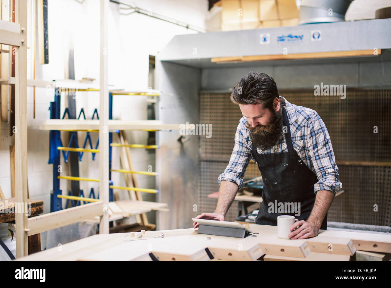 Cropped shot of mid adult craftsman using digital tablet in organ workshop - Stock Image