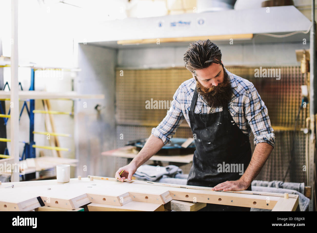 Cropped shot of mid adult craftsman measuring wood in organ workshop - Stock Image