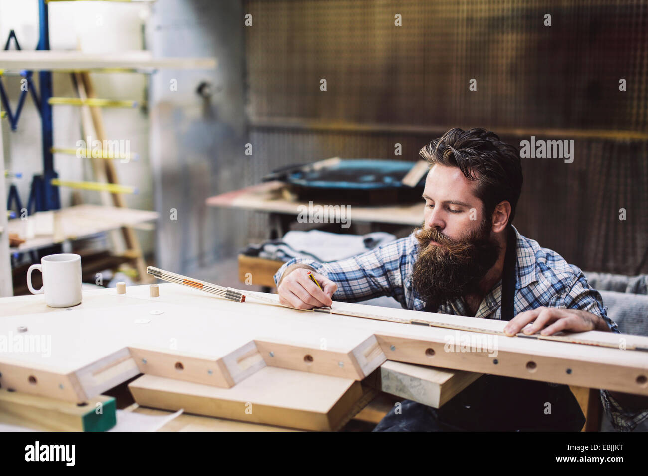 Cropped shot of mid adult craftsman measuring wood component in organ workshop - Stock Image
