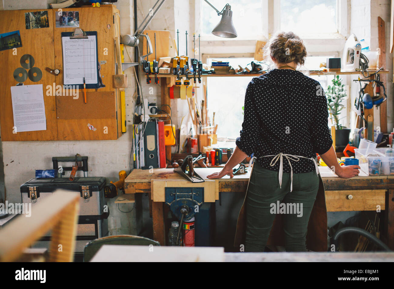 Rear view of young craftswoman at workbench in pipe organ workshop - Stock Image