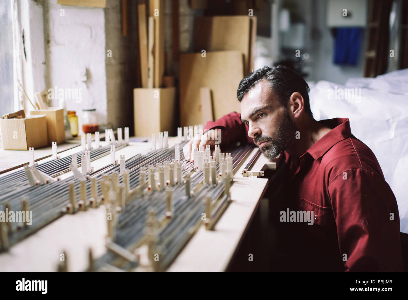 Mature craftsman checking organ pipes in pipe organ workshop - Stock Image