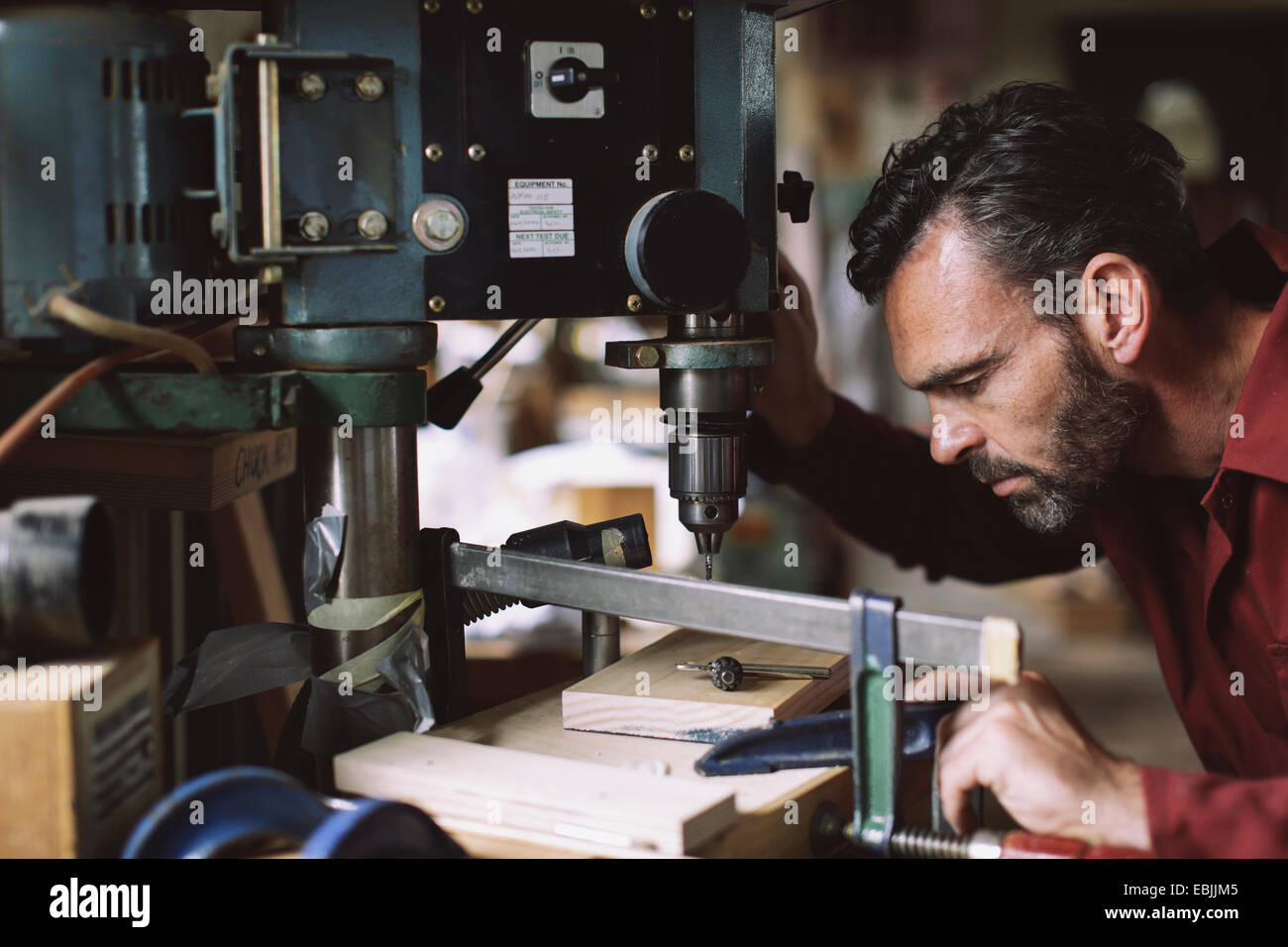 Mature craftsman drilling component in pipe organ workshop - Stock Image