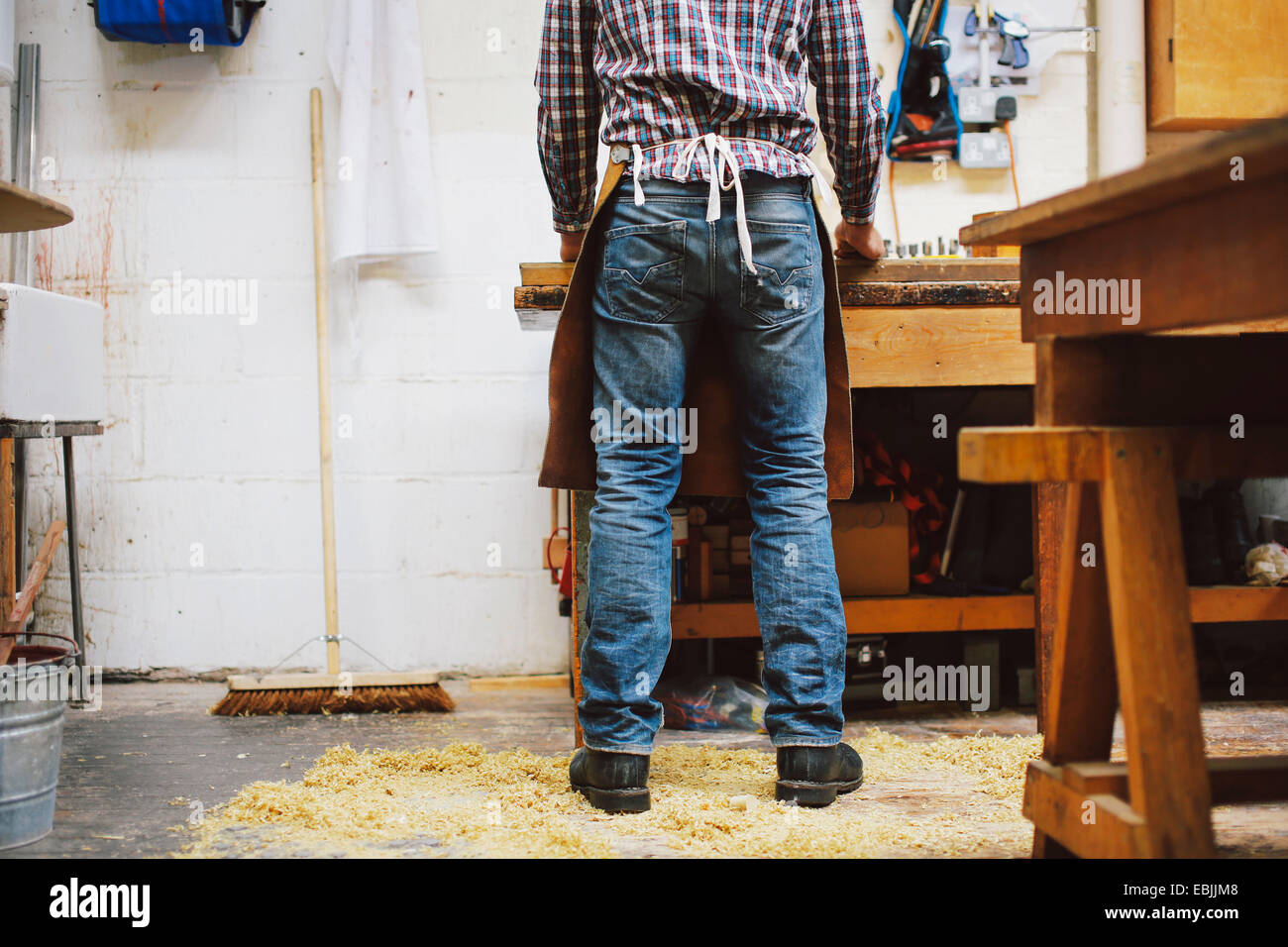 Cropped view of mature craftsman at workbench in pipe organ workshop Stock Photo
