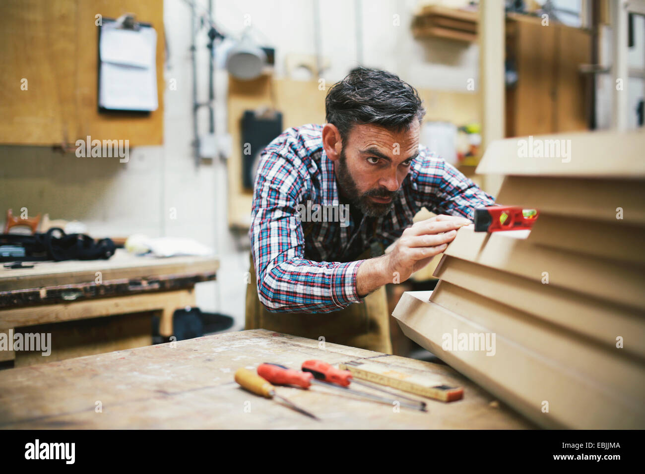 Mature craftsman using spirit level in pipe organ workshop - Stock Image