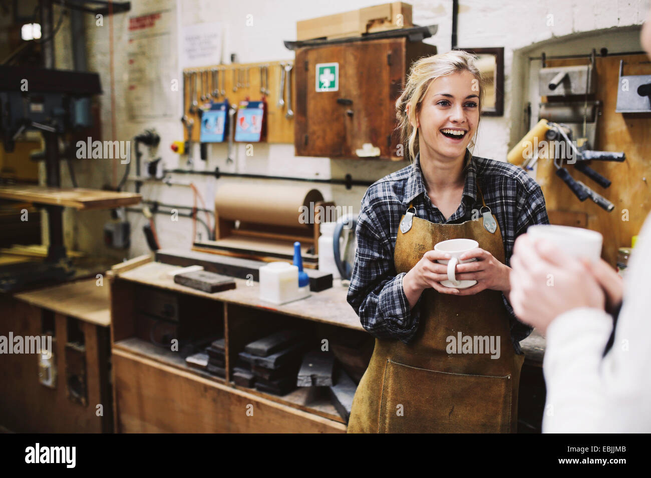 Two young craftswomen chatting in pipe organ workshop - Stock Image