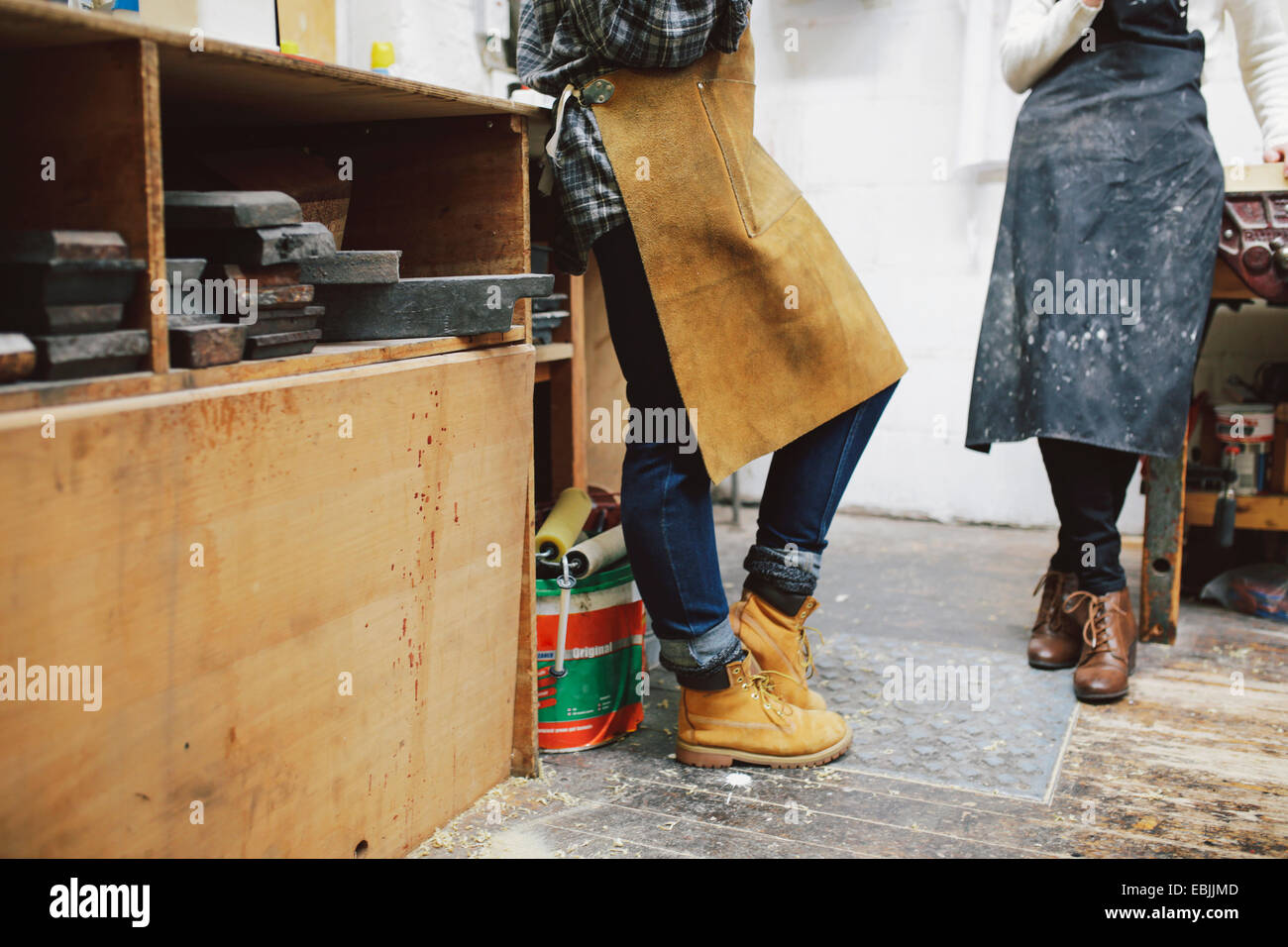 Cropped view of two young craftswomen in pipe organ workshop - Stock Image