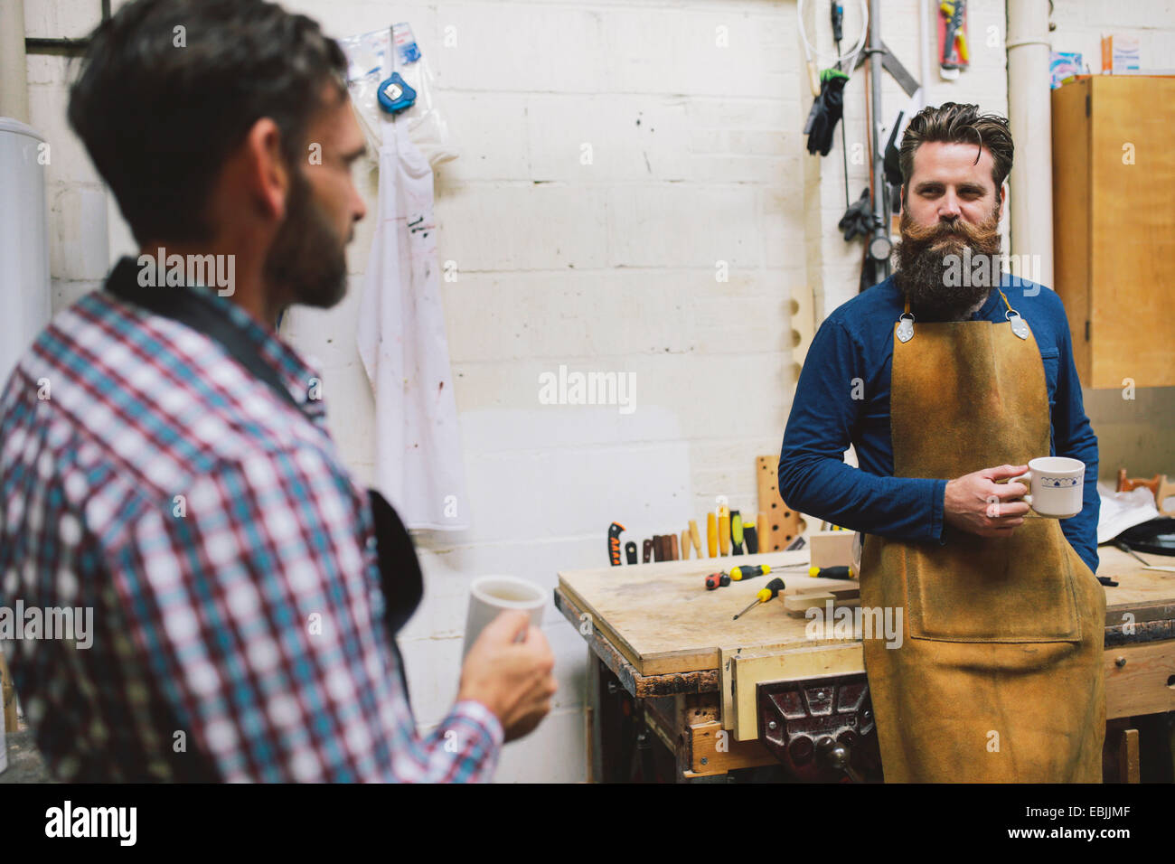 Two craftsmen chatting in pipe organ workshop - Stock Image