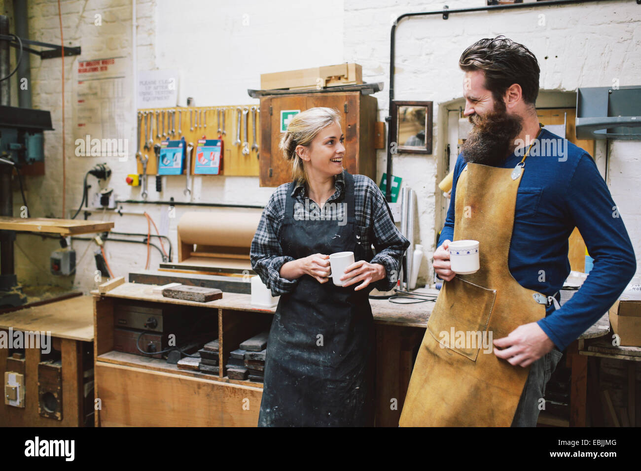 Craftsman and woman chatting in pipe organ workshop - Stock Image